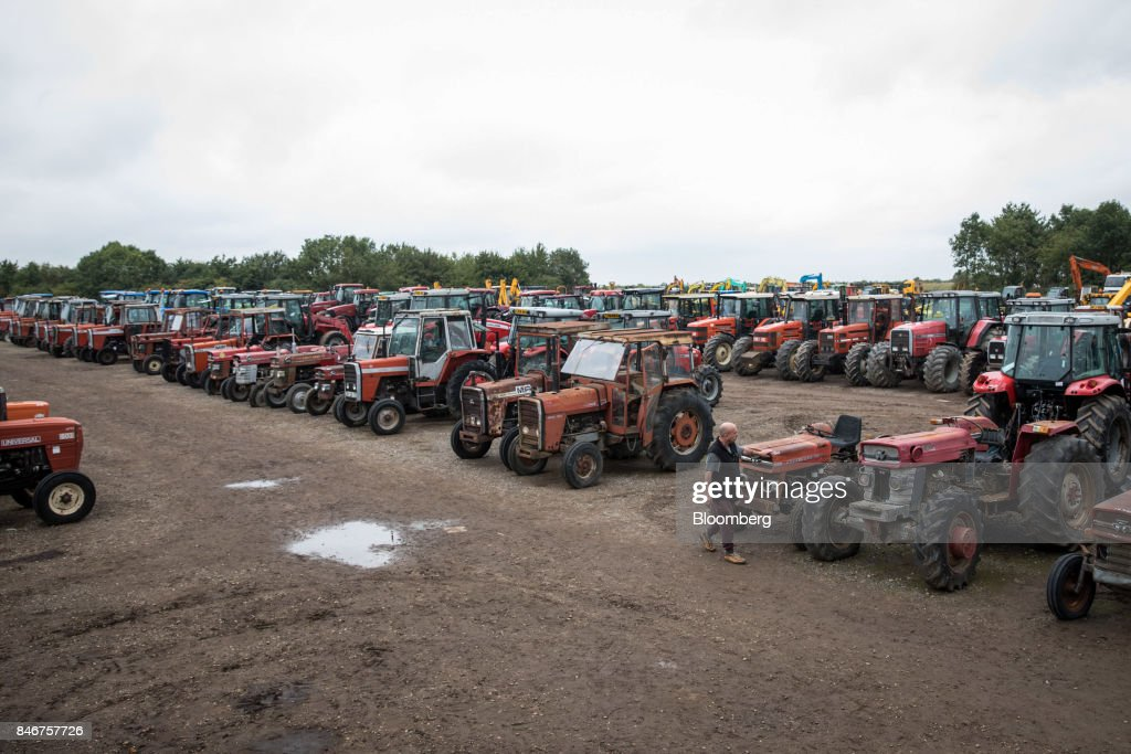 A visitor inspects tractors, manufactured by Massey Ferguson Corp., before they are put up for auction at the Cheffins Cambridge Machinery Sales monthly machinery and plant auction in Sutton, U.K., on Monday, Sept. 4, 2017. The debate over food andfarmingpolicy after Brexit has heated up recently, with Environment Secretary Michael Gove telling BBC Radio 4 that the U.K wouldnt lower its animal welfare or environmental standards to achieve any new trade deals. Photographer: Simon Dawson/Bloomberg via Getty Images