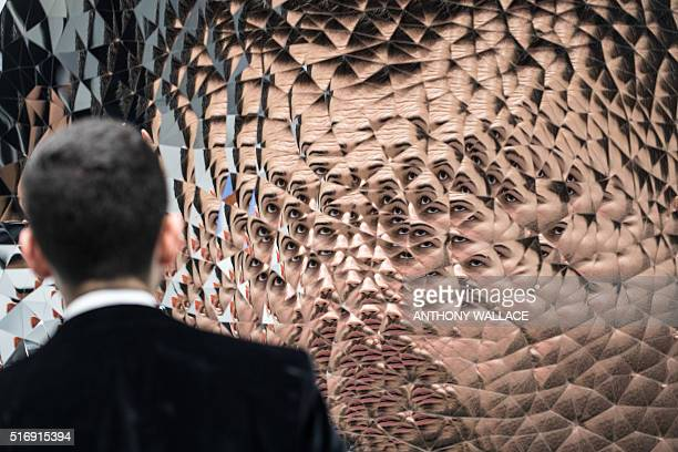 TOPSHOT A visitor interacts with Anish Kapoor's 'Random Triangle Mirror' during the press preview for Art Basel in Hong Kong on March 22 before it...