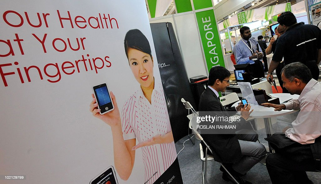 A visitor is briefed by an exhibitor on a EPI Life smartphone that detect a person's abnormal heart rhythm, at the CommunicAsia 2010 conference and exhibition show in Singapore on June 16, 2010. With EPI Life, a 106-gram touch-screen phone on exhibit at a technology conference in Singapore, your electrocardiogram (ECG) chart will be literally at your fingertips within minutes. An ECG, usually conducted at a clinic or hospital, can detect a person's abnormal heart rhythm, allowing the individual to seek immediate medical attention.