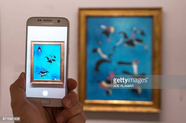 A visitor is looking at an animation as he points his smartphone at Joan Miro's painting 'Birds and Insects' using the Artvive app at Albertina...