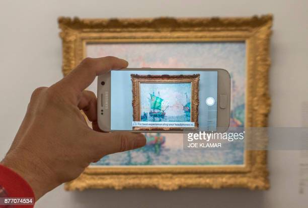 A visitor is looking at an animation as he points his smartphone at French painter Paul Signac's painting 'Venice The Pink Cloud' using the Artvive...