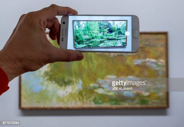 A visitor is looking at an animation as he points his smartphone at French painter Claude Monet's painting 'Water Lilies' using the Artvive app at...