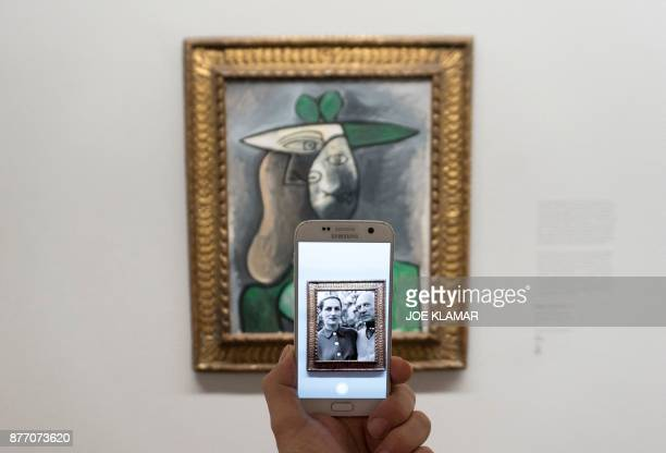 A visitor is looking at an animation showing Spanish artist Pablo Picasso and his daughter as he points his smartphone at Pablo Picasso's 'Woman in a...