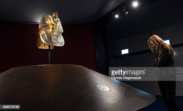 A visitor is looking at the burial mask of Egyptian Pharaoh Tutankhamun during the 'Tutanchamun Sein Grab und die Schaetze' Exhibition Preview at...