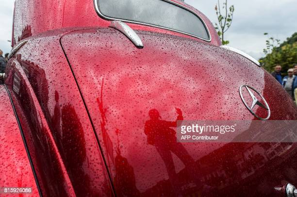 A visitor is reflected on a vintage Mercedes car displayed during the 12th Old Timer Fest on July 17 2017 in the historic city of Prizren in southern...