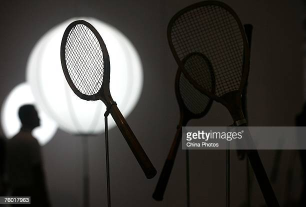 A visitor is reflected on a wall as he views tennis rackets from past Olympic Games during the IOC Olympic Treasure Exhibition China Tour part of...