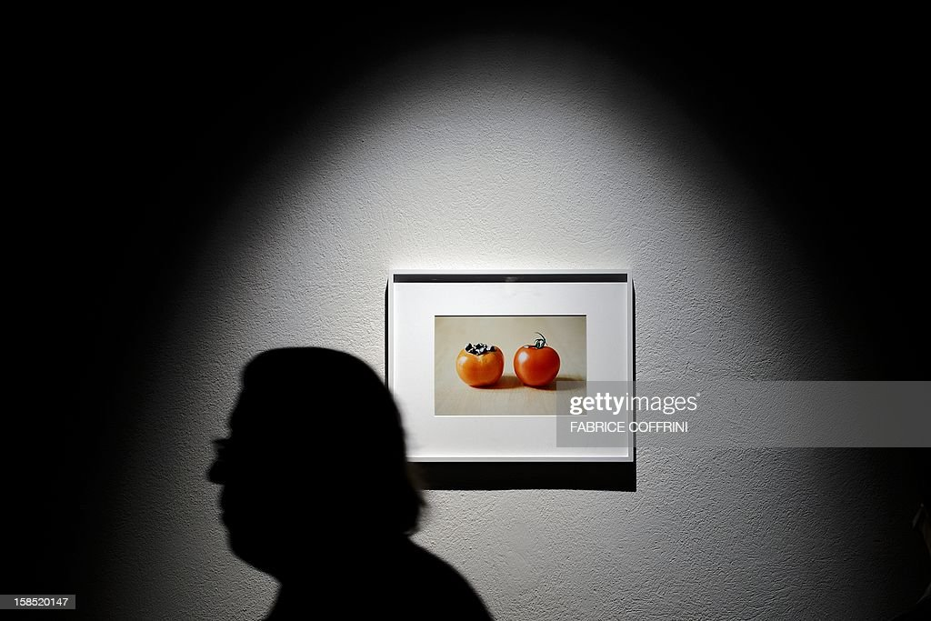 A visitor is seen in silhouette as he walks past a photography by Japanese born artist Shimabuku entitled 'Kaki and Tomato' during the press preview of the exhibition 'Food' on December 18, 2012 at the Ariana museum in Geneva. The international travelling contemporary art exhibition will be presented later in Milan, Sao Paulo and Marseille.