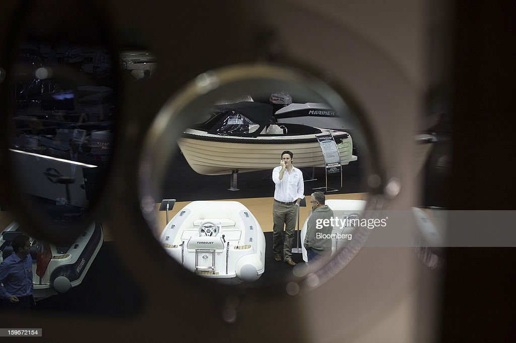 A visitor is seen through the porthole of a luxury Sunseeker International Ltd. yacht as he stands amongst a display of Williams Performance Tenders at the Tullet Prebon London Boat Show 2013 at the ExCeL center in London, U.K., on Wednesday, Jan. 16, 2013. The show, Europe's first in 2013, will showcase new sailing craft from dinghies to luxury yachts, and runs Jan. 12-20. Photographer: Simon Dawson/Bloomberg via Getty Images