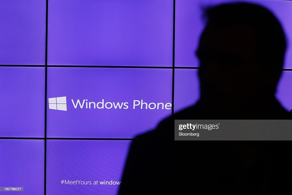 A visitor is silhouetted in front of a video advertisement for the Windows Phone at a media event at the Hotel Rey San Carlos during the Mobile World Congress in Barcelona, Spain, on Tuesday, Feb. 26, 2013. The Mobile World Congress, where 1,500 exhibitors converge to discuss the future of wireless communication, is a global showcase for the mobile technology industry and runs from Feb. 25 through Feb. 28. Photographer: Simon Dawson/Bloomberg via Getty Images
