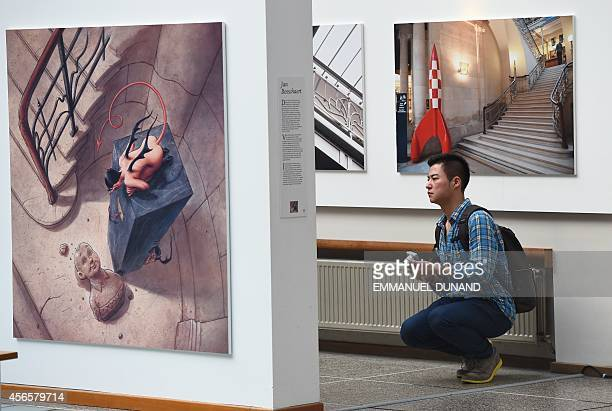 A visitor kneels by a plate by Belgian cartoonist Jan Bosschaert in the 'Centre Belge de la Bande Dessinee' on October 3 2014 in Brussels as it marks...