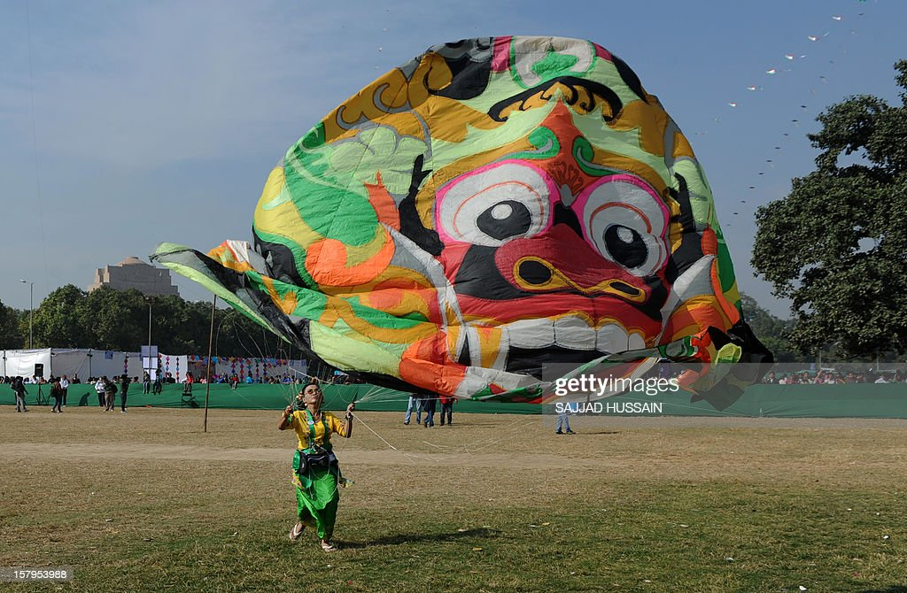 A visitor launches a kite during the Delhi International Kite Festival 2012 on the lawns of the India Gate monument in New Delhi on December 8, 2012. The event, organised by Delhi Tourism, is being held in the Indian capital on December 8 - 9.