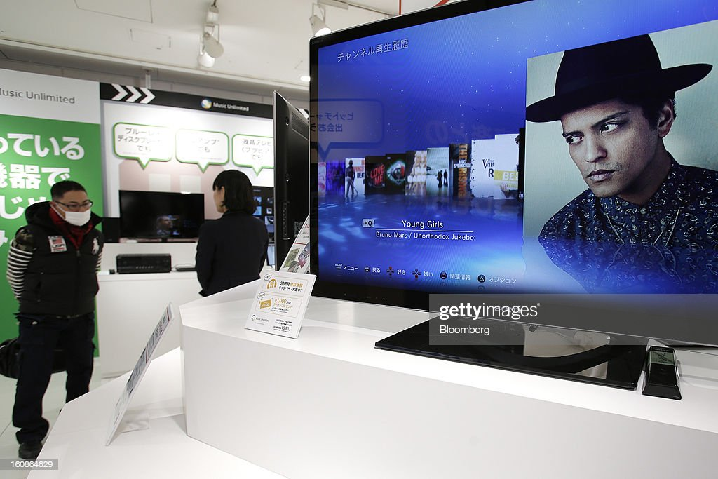 A visitor, left, looks at Sony Corp.'s products displayed at the company's showroom in Tokyo, Japan, on Thursday, Feb. 7, 2013. Sony, Japan's biggest consumer-electronics exporter, reported an eighth consecutive quarterly loss on waning demand for TVs and consumer preferences for devices from Apple Inc. and Samsung Electronics Co. Photographer: Kiyoshi Ota/Bloomberg via Getty Images