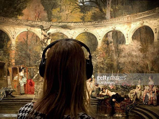 A visitor listens to an audio guide as she watches a painting on display at the Hermitage museum in Amsterdam on June 14 2012 The museum is...