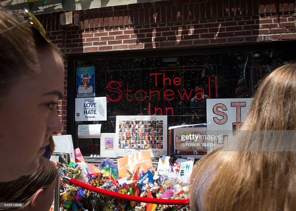Visitor look at a memorial at the Stonewall Inn as Mayor Bill de Blasio joins elected officials, advocates and New Yorkers in designating Stonewall Inn a National Monument, on June 27, 2016 in New York. / AFP / Bryan R. Smith