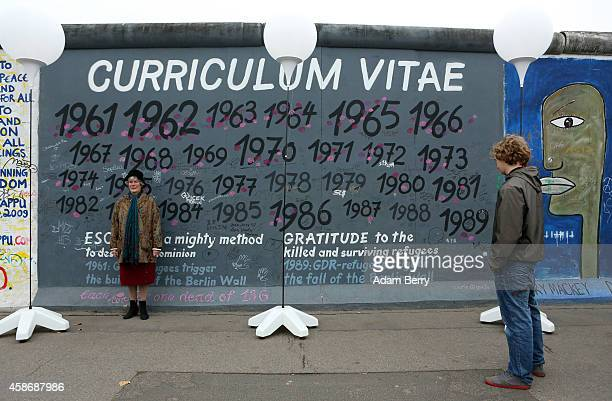 A visitor look at graffiti as another poses at East Side Gallery a section of the former Berlin Wall during celebrations for the 25th anniversary of...