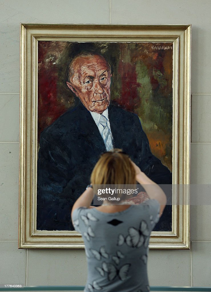 A visitor look stanps a photo of a portrait of former German chancellor Konrad Adenauer during the annual open-house day at the Chancellery on August 25, 2013 in Berlin, Germany. Approximately 150,000 visitors took advantage of the annual event held at the Chancellery and German government ministries to get an inside glimpse.