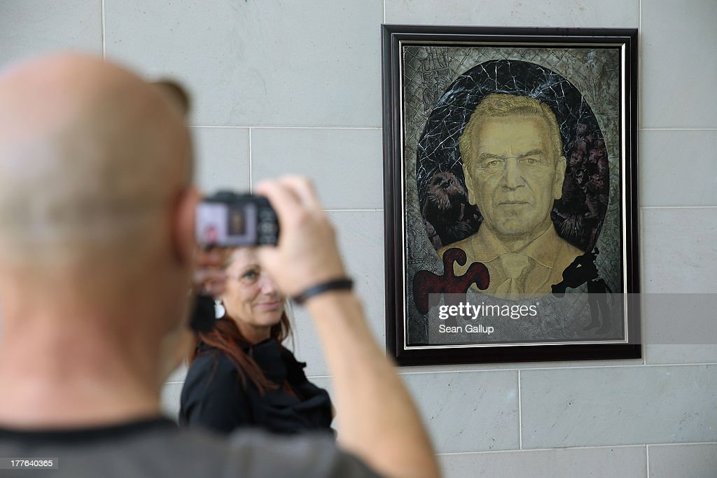 A visitor look stanps a photo of a portrait of former German chancellor Gerhard Schroeder during the annual open-house day at the Chancellery on August 25, 2013 in Berlin, Germany. Approximately 150,000 visitors took advantage of the annual event held at the Chancellery and German government ministries to get an inside glimpse.