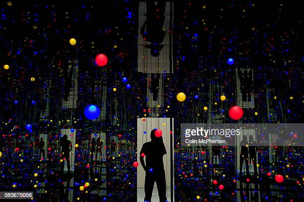 A visitor looking at 'Gleaming Lights of the Soul' a mixed media installation by veteran Japanese artist Yayoi Kusama on display at Pilkington's one...
