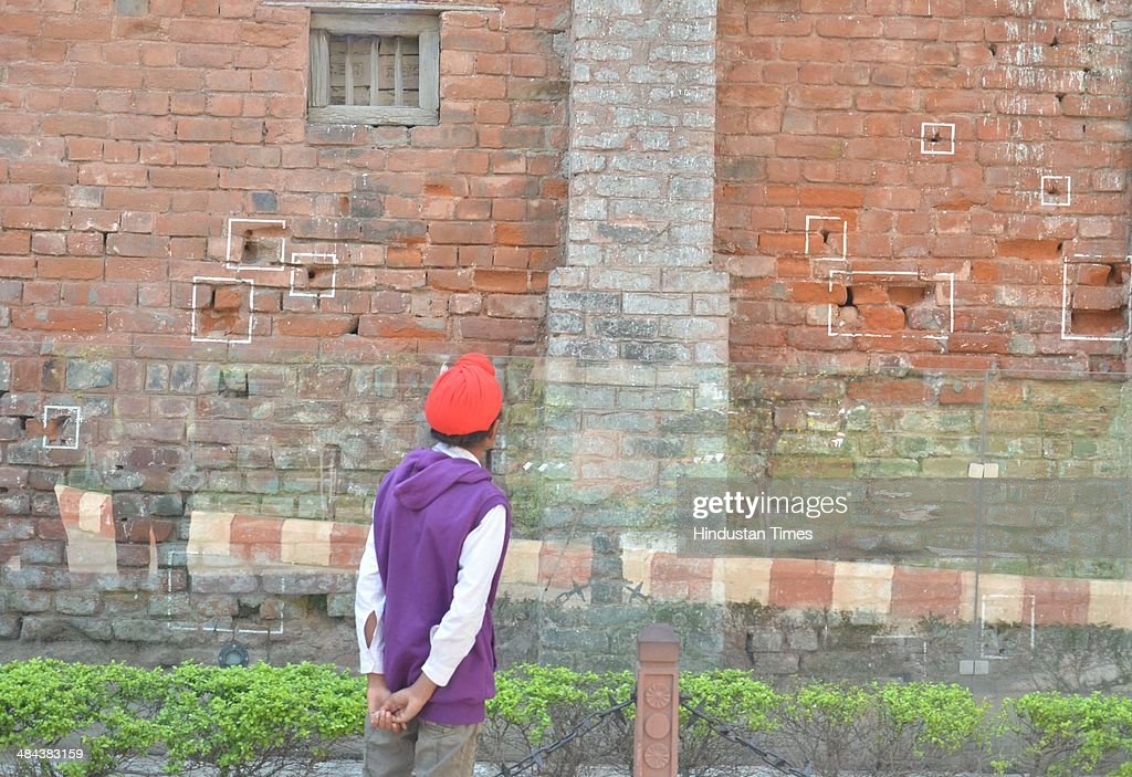 A visitor looking at the bullet marks on a wall on the eve of 95th anniversary of Jallianwala Bagh massacre at Jallianwala Bagh on April 12 2014 in...