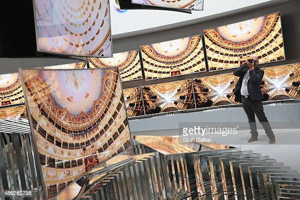 A visitor looks at 4K SUHD curved televisons at the Samsung stand during a press day at the 2015 IFA consumer electronics and appliances trade fair...