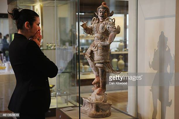 A visitor looks at a 7th or 8th century 'Painted pottery or tomb Guardian' during a press call at the British Museum on January 8 2014 in London...