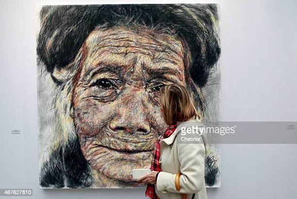 A visitor looks at a artwork by Vietnamian artist Hom Nguyen entitled 'Grandmere raconte moi' during the 2015 Art Paris Art Fair at the Grand Palais...
