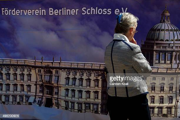 A visitor looks at a banner showing a depiction of the Berlin City Palace at the construction site in the city center on June 1 2014 in Berlin...