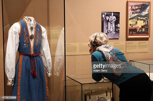 A visitor looks at a bunad a traditional Norwegian rural dress sewn by Ingebjorg Aasen directly after the War during a visit to the exhibition '1945...