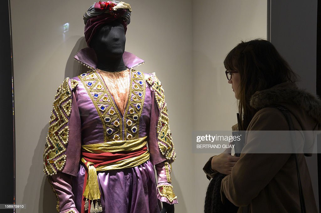 A visitor looks at a costume displayed during the exhibition entitled 'Les Mille et une Nuits' (The thousand and one nights) at the Arab World Institute (IMA) on November 26, 2012 in Paris. The event runs until April 28, 2013.