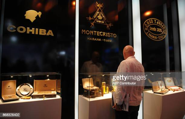 A visitor looks at a Cuban cigar stand during the 35th Havana International Fair on October 30 2017 in Havana / AFP PHOTO / YAMIL LAGE