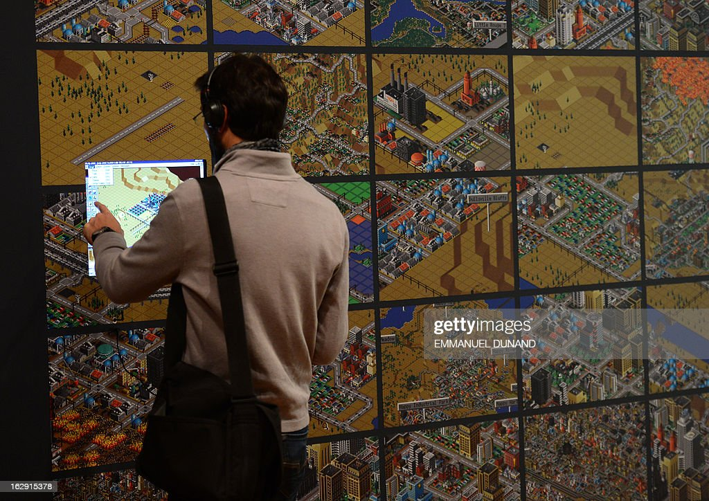 A visitor looks at a demonstration of the video game SimCity (2000) during an exhibition preview featuring 14 video games acquired by The Museum of Modern Art (MoMA) in New York, March 1, 2013. The MoMA acquired 14 video games entering its collection as part of an ongoing research on interaction design.
