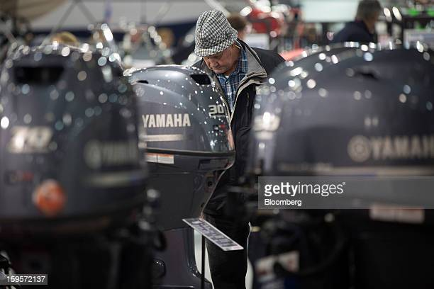 A visitor looks at a display of outboard motors manufactured by Yamaha Motor Co during the Tullet Prebon London Boat Show 2013 at the ExCeL center in...