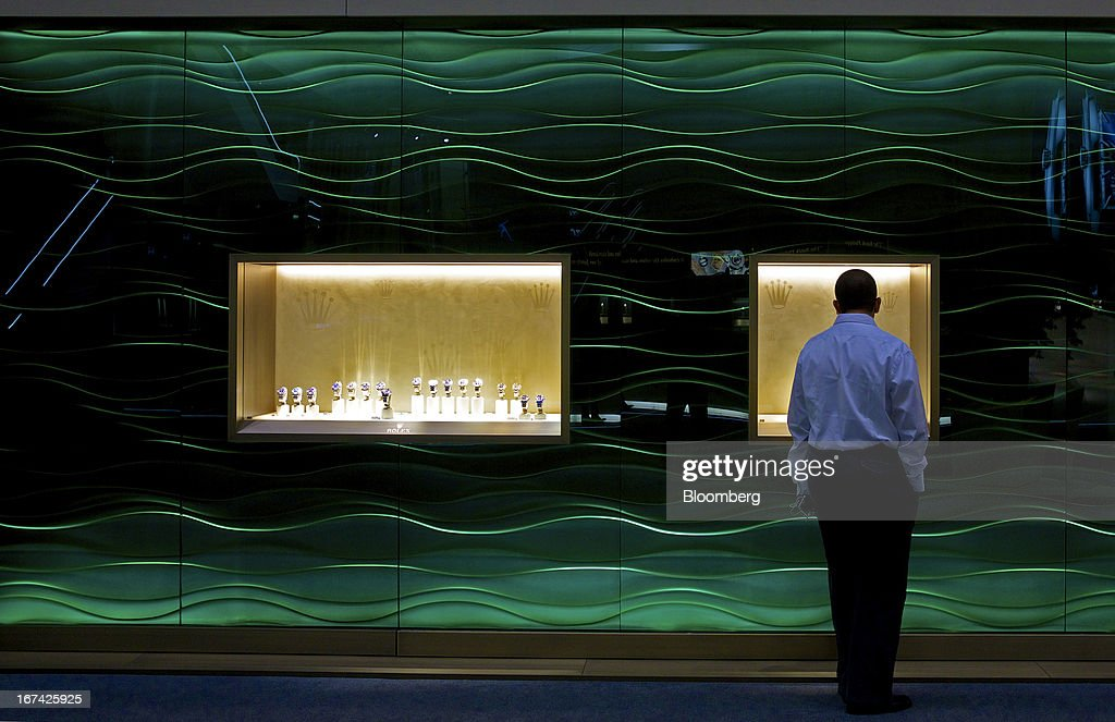 A visitor looks at a display of wristwatches displayed at the Rolex Group booth during the Baselworld watch fair in Basel, Switzerland, on Thursday, April 25, 2013. The annual fair attracts 2,000 companies from the watch, jewelry and gem industries to show their new wares to more than 100,000 visitors. Photographer: Gianluca Colla/Bloomberg via Getty Images