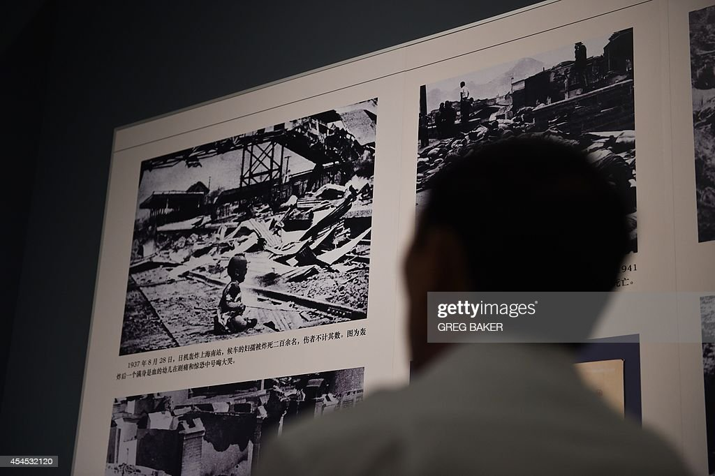 A visitor looks at a famous photo of a baby crying at Shanghai South Railway Station after a Japanese bombing attack on the city in 1937, at an exhibition about World War II in Beijing on September 3, 2014. Chinese President Xi Jinping and all six other members of the Politburo Standing Committee, the country's most powerful body, made a rare public appearance Sept 3 to commemorate 69 years since Japan's surrender at the end of World War II. AFP PHOTO/Greg BAKER -- RESTRICTED TO EDITORIAL USE, MANDATORY MENTION OF THE ARTIST UPON PUBLICATION, TO ILLUSTRATE THE EVENT AS SPECIFIED IN THE CAPTION