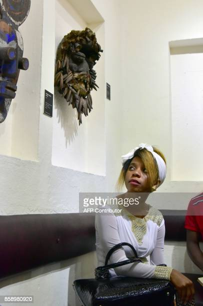 A visitor looks at a mask as she visits the Civilisation Museum of Abidjan on September 29 2017 during the first exhibition called 'Renaissance'...