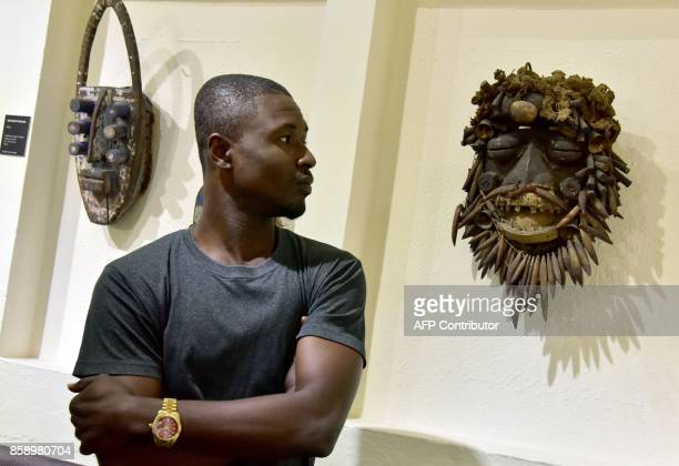 A visitor looks at a mask exhibited at the Civilisation Museum of Abidjan on September 29 2017 during the first exhibition called 'Renaissance'...