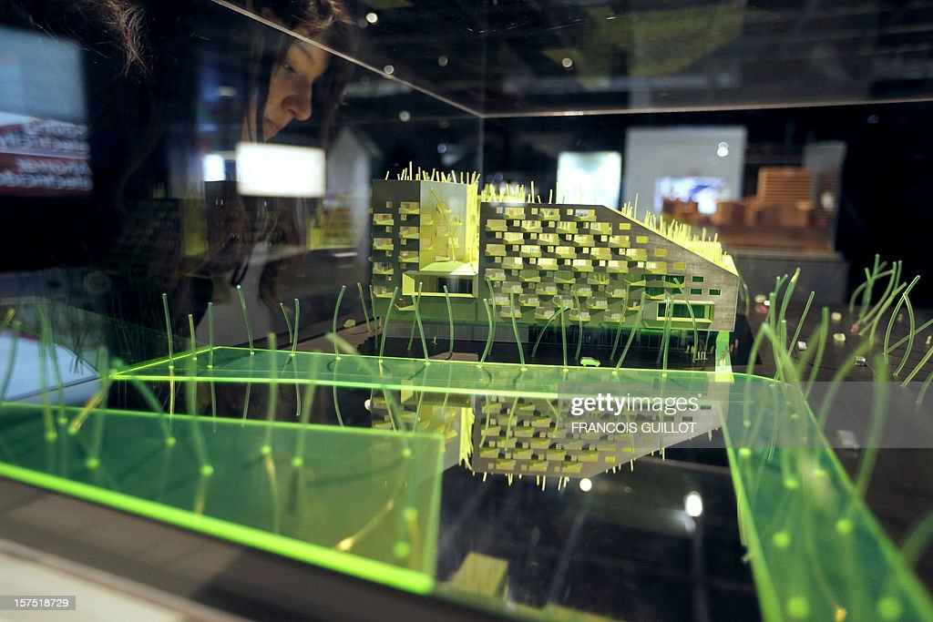 A visitor looks at a model of 120 social housing and business units in an eco-district in Saint-Ouen, a Paris suburb by X-TU architects office which is displayed at the Cite des Sciences et de l'Industrie in Paris on December 4, 2012, as part of the exhibition 'Habiter demain' (Reinventing our homes) focused on the social and human aspects of housing and the new way to build home of the future and renovate houses. The event runs from December 4, 2012 to November 13, 2013.