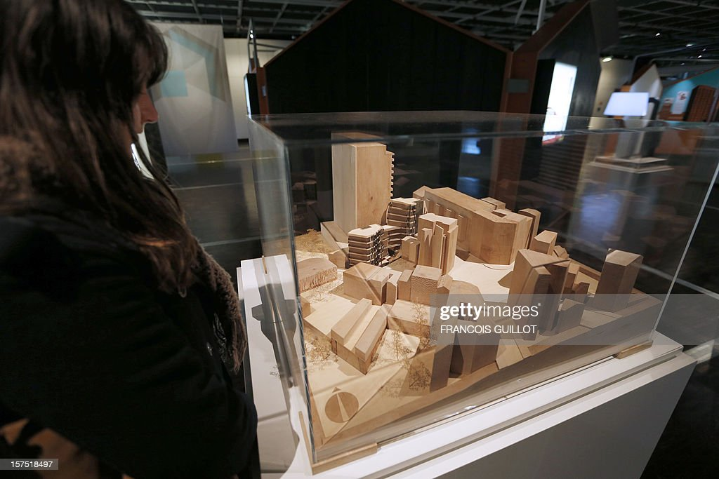 A visitor looks at a model of a new 19 housing and business units in Paris 20th district by architects Marie-Eve Bidard and Shirin Raissi which is displayed at the Cite des Sciences et de l'Industrie in Paris on December 4, 2012, as part of the exhibition 'Habiter demain' (Reinventing our homes) focused on the social and human aspects of housing and the new way to build home of the future and renovate houses. The event runs from December 4, 2012 to November 13, 2013.