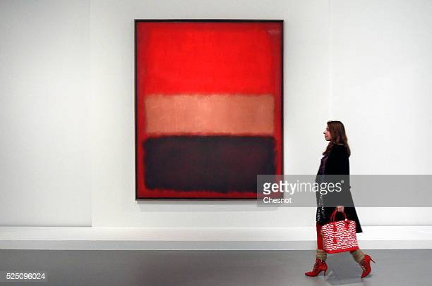 A visitor looks at a painting Black Ochre Red Over Red of Mark Rothko as part of the opening of the exhibition 'Keys to a Passion' at the Louis...