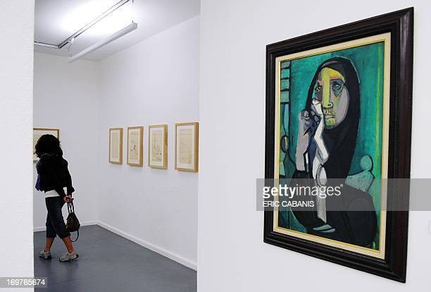 A visitor looks at a painting by Edouard Pignon a French painter from the 'Ecole de Paris' during an exhibition in his honor at the Modern Art museum...