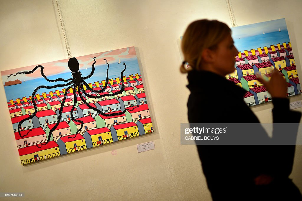 A visitor looks at a painting by Italian artist and former killer and drug trafficker for the Cosa Nostra mafia, Gaspare Mutolo, during the opening of an exhibition on January 18, 2013 in Rome. Mutolo, 72 year-old repentant mafioso is showing his work dedicating to the Sicilian city of Palermo. AFP PHOTO / GABRIEL BOUYS TO GO WITH AFP STORY - RESTRICTED TO EDITORIAL USE, MANDATORY CREDIT OF THE ARTIST, TO ILLUSTRATE THE EVENT AS SPECIFIED IN THE CAPTION
