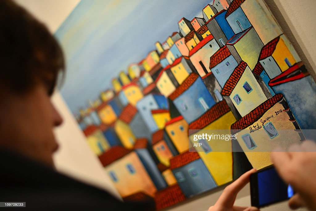 A visitor looks at a painting by Italian artist and former killer and drug trafficker for the Cosa Nostra mafia, Gaspare Mutolo, during the opening of an exhibition on January 18, 2013 in Rome. Mutolo, 72 year-old repentant mafioso is showing his work dedicating to the Sicilian city of Palermo.