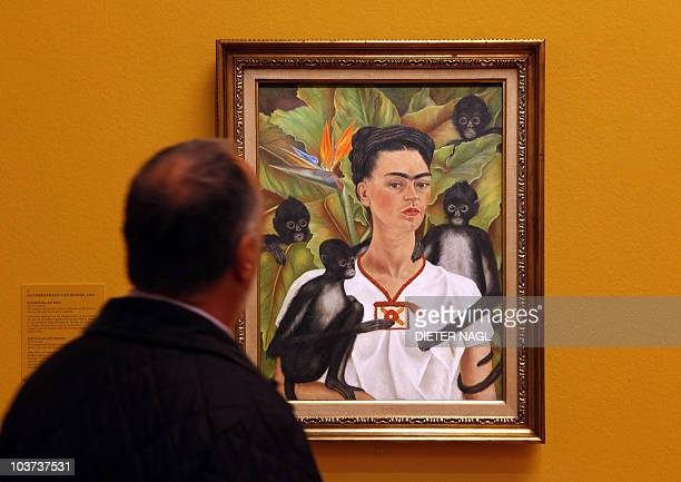 A visitor looks at a painting by Mexican artist Frida Kahlo titled 'SelfPortrait with monkeys' during the opening of a show of her works on August 31...