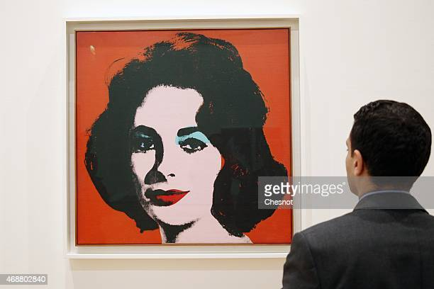 A visitor looks at a painting by US artist Andy Warhol entitled 'Liz' during the press opening of the exhibition 'Icones Americaines' at the Grand...