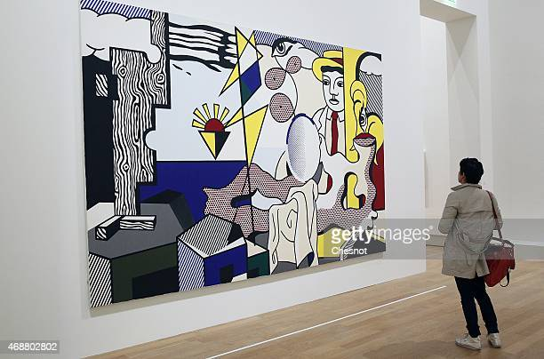 A visitor looks at a painting by US Roy Lichtenstein entitled 'Figures with sunset' during the press opening of the exhibition Icones Americaines at...