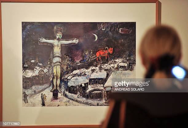 Visitor looks at a painting 'Christ and Village Under the Snow' by FrancoRussian avantgarde painter Marc Chagall as part of the exhibition 'Chagall...