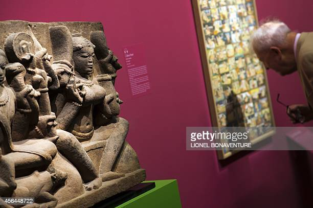 A visitor looks at a painting displayed during the exhibition The KamaSutra spirituality and erotism in Indian art at the Paris' pinacotheque on...
