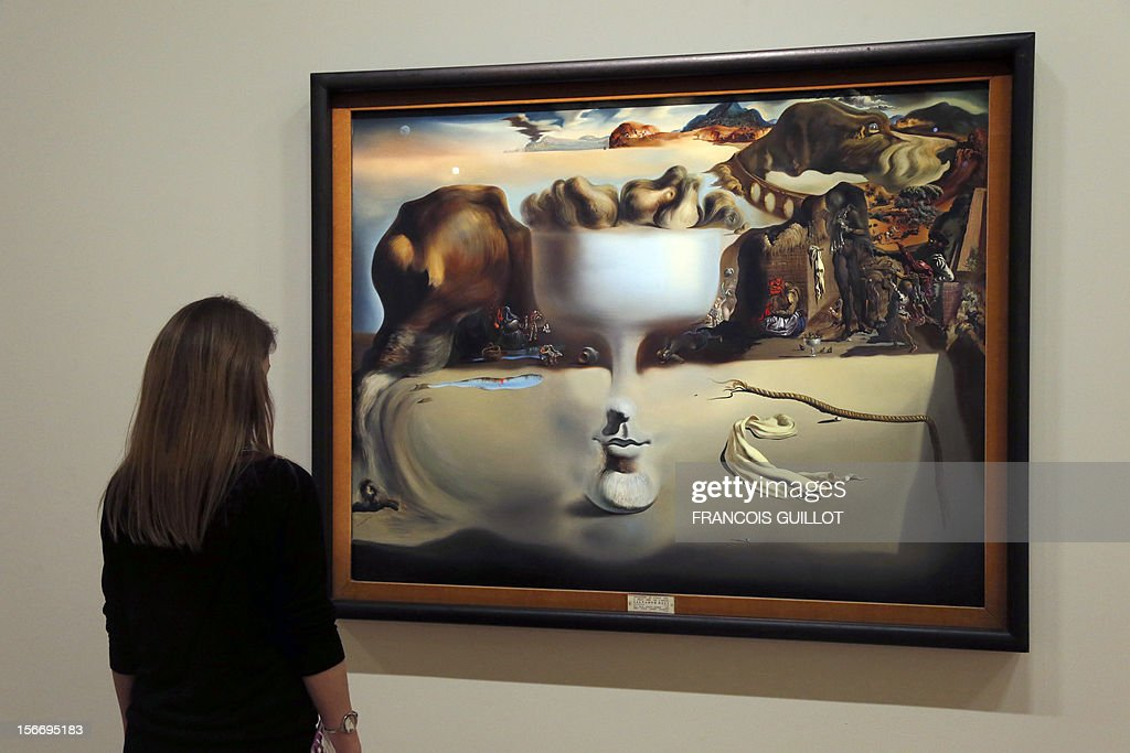 A visitor looks at a painting entitled 'Apparition d'un visage et d'un compotier sur une plage' (Apparition of Face and Fruit Dish on a Beach) by Spanish surrealist artist Salvador Dali during an exhibition devoted to his work at the Centre Pompidou contemporary art center (aka Beaubourg) on November 19, 2012 in Paris. More than 30 years after the first retrospective in 1979, the event gathers more than 200 art pieces and runs until March 13, 2013.