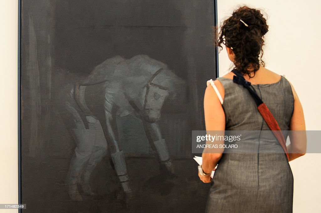 A visitor looks at a painting entitled 'Gran Practice' by Romanian artist Victor Man on June 25, 2013 during an exhibition at the Villa Medici, the headquarters of the French Academy in Rome.