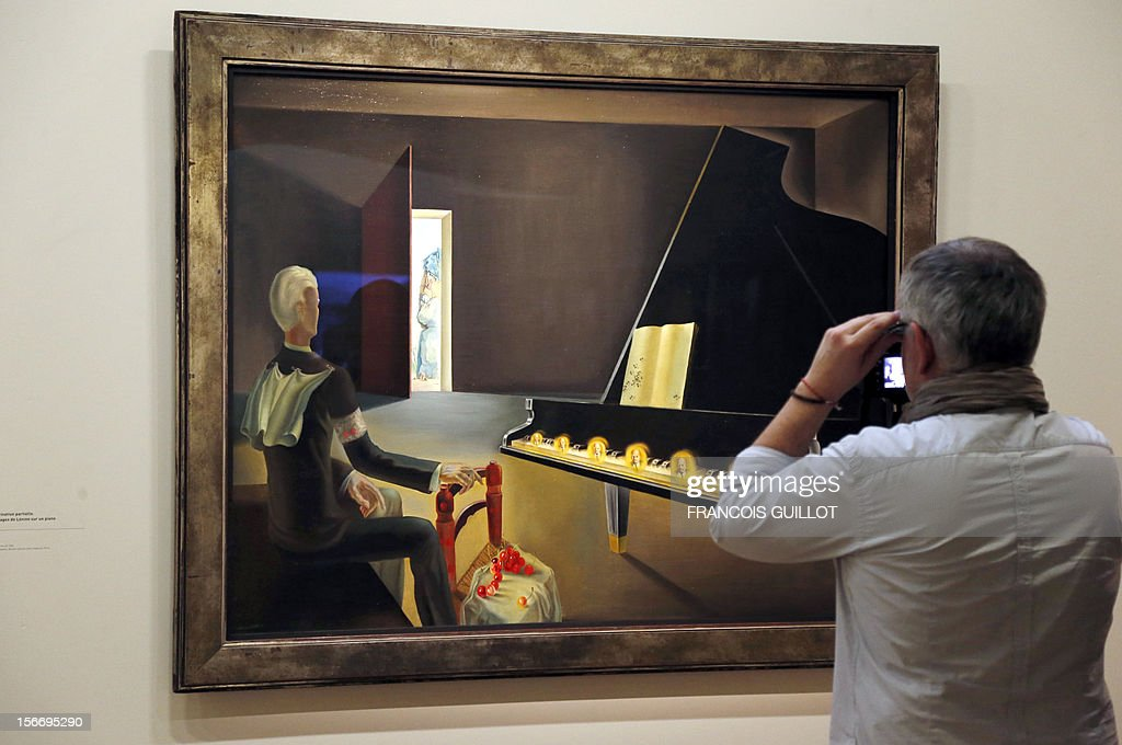 A visitor looks at a painting entitled 'Hallucination partielle, Six images de Lenine sur un Piano' (Six Apparitions of Lenin on a Grand Piano), 1931, by Spanish surrealist artist Salvador Dali during an exhibition devoted to his work at the Centre Pompidou art center (aka Beaubourg) on November 19, 2012 in Paris. More than 30 years after the first retrospective in 1979, the event gathers more than 200 art pieces and runs until March 13, 2013.